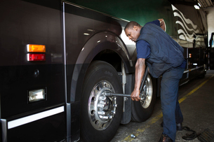 Mechanic screwing lug of bus wheel with wrenchの写真素材 [FYI03668667]