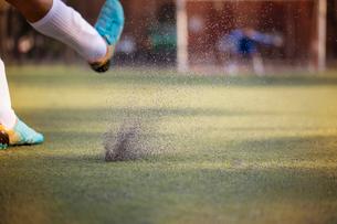 Soccer player kicking ball towards goalieの写真素材 [FYI03669072]