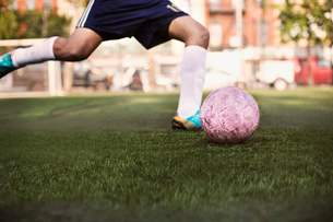 Soccer player kicking ball low sectionの写真素材 [FYI03669075]