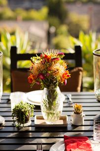 Flowers in vase on table of outdoor restaurantの写真素材 [FYI03669458]