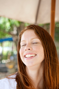 Woman under parasol smilingの写真素材 [FYI03670023]