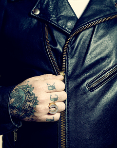 Close up of tattooed hand zipping jacketの写真素材 [FYI03670057]