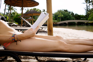 Mid section of woman lying on lounge chair and reading bookの写真素材 [FYI03670488]