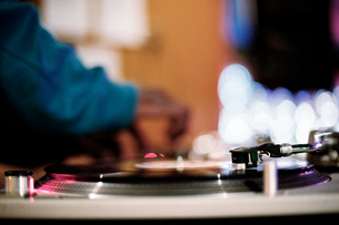 Record and needle with DJ in backgroundの写真素材 [FYI03670606]