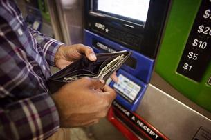 Hands of man standing in front of ATM holding open walletの写真素材 [FYI03671386]
