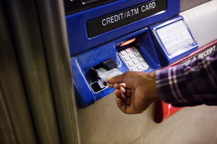 Hand of man inserting credit card into ATM slotの写真素材 [FYI03671387]