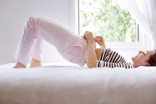 Woman lying on bed and festering on pantsの写真素材 [FYI03671492]