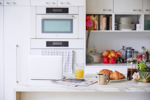 Orange juice, newspaper, croissants and laptop on kitchen counterの写真素材 [FYI03671834]