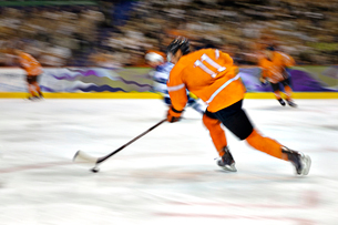 Ice hockey player skating with puckの写真素材 [FYI03672138]