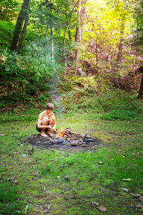 Young boy(14-15) starting camp fireの写真素材 [FYI03672239]