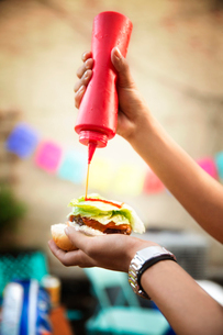 Person pouring mustard on hamburgerの写真素材 [FYI03672789]