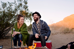 Man and woman sitting by camp fire in afternoon sand and rockの写真素材 [FYI03673162]