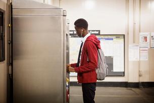 Teenage boy (14-15) choosing snack from vending machineの写真素材 [FYI03673616]