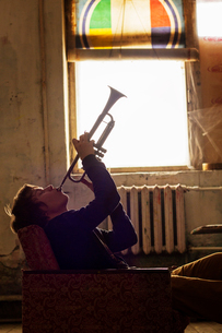 Young man sitting in armchair playing trumpet in dilapidated roomの写真素材 [FYI03674053]