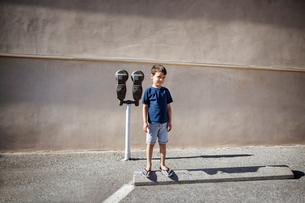 Boy (4-5) standing next to parking meterの写真素材 [FYI03675241]