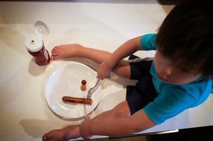 Boy eating sausageの写真素材 [FYI03675659]