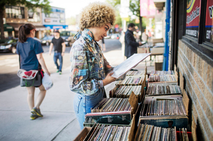 Young woman choosing record in front of store,の写真素材 [FYI03677086]