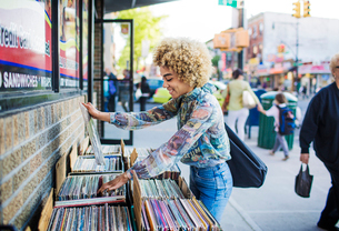 Young woman choosing record in front of store,の写真素材 [FYI03677087]