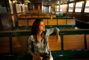Female sitting on wooden sit in empty tourboat looking at viewの写真素材 [FYI03677594]