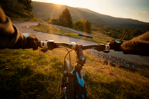 Wide angle view of biker's hands holding handlebars road and landscape with hillsの写真素材 [FYI03679207]