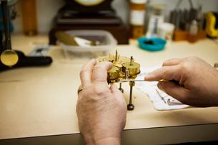 Hands of clockmaker repairing clockの写真素材 [FYI03679363]