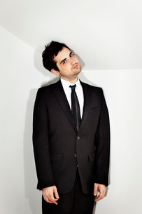 Portrait of young businessman in cornerの写真素材 [FYI03679622]