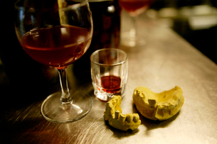 Dentures and wineglass on bar counterの写真素材 [FYI03680136]