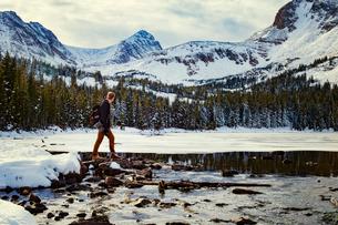 USA, Colorado, Nederland, Young man crossing frozen water reservoirの写真素材 [FYI03681963]