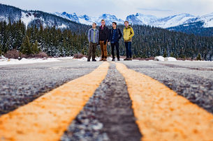 USA, Colorado, Nederland, Four young men standing on roadの写真素材 [FYI03681966]