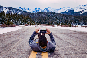 USA, Colorado, Nederland, Young man lying down on road taking photoの写真素材 [FYI03681968]