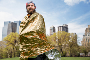 Man in park wrapped in emergency blanketの写真素材 [FYI03682749]