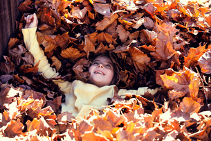 Girl (8-9) relaxing in heap of autumn leavesの写真素材 [FYI03683361]