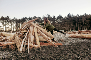 Mid adult woman standing on one leg by heap of logの写真素材 [FYI03683598]