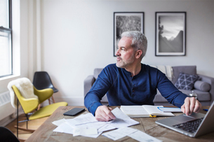 Thoughtful man looking away while calculating home finances at tableの写真素材 [FYI03683849]
