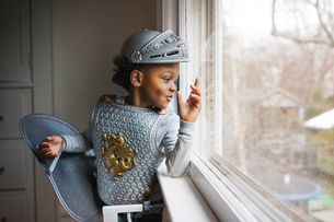 Curious boy dressed up in armor costume looking out through window at homeの写真素材 [FYI03684037]