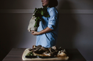 Woman carrying grocery bag while walking by table with chopped lamb on cutting boardの写真素材 [FYI03684111]