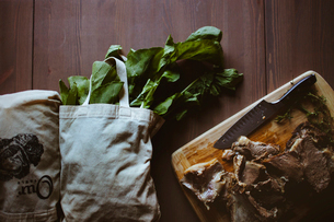 Overhead view of chopped lamb and grocery bags on tableの写真素材 [FYI03684114]