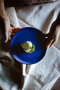 Overhead view of woman holding cucumber and rice wrap in plate at dining tableの写真素材 [FYI03684125]