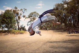 Male martial artist performing back flip on dirt roadの写真素材 [FYI03684149]