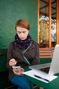 Teenager girl using smart phone while sitting at sidewalk cafeの写真素材 [FYI03684164]