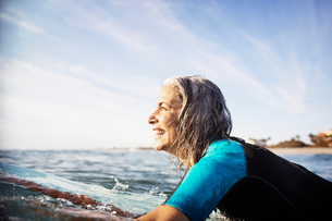 Side view of happy mature woman lying on surfboard in seaの写真素材 [FYI03684270]