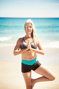 Determined mature woman practicing yoga in tree pose at Delray beachの写真素材 [FYI03684281]