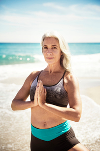 Portrait of confident woman practicing yoga in tree pose at Delray beachの写真素材 [FYI03684282]