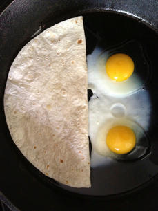 Overhead view of flatbread and fried eggs in panの写真素材 [FYI03684404]