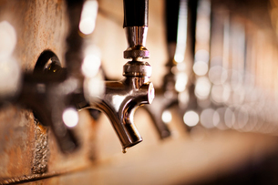 Close-up of metallic beer taps at barの写真素材 [FYI03684506]