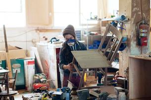 Female carpenter examining wooden chair in workshopの写真素材 [FYI03684614]