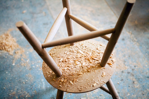 High angle view of shavings of upside down wooden table in workshopの写真素材 [FYI03684631]