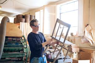 Male carpenter examining wooden chair in workshopの写真素材 [FYI03684676]