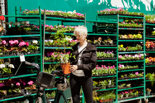 Woman looking at potted plant in retail display at shopの写真素材 [FYI03684678]