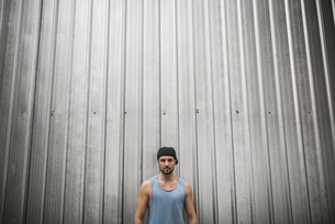 Serious man standing against metallic wallの写真素材 [FYI03684786]